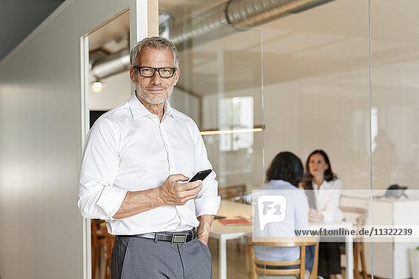 Zuversichtlicher Geschäftsmann mit Handy im Büro mit Mitarbeitern im Hintergrund