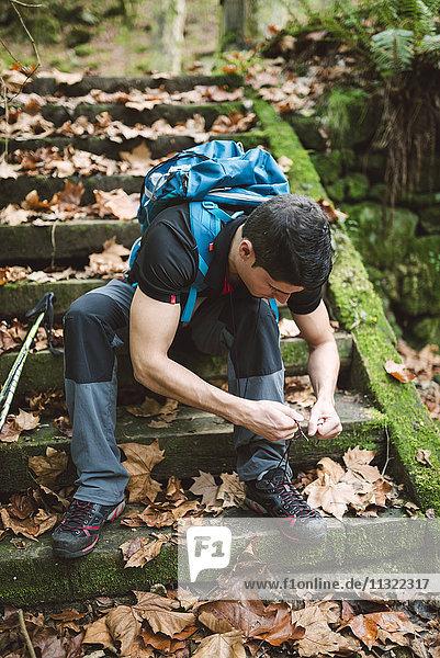 Wanderer sitzt auf einer Treppe und schnürt seine Schuhe.