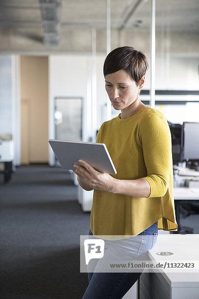 Geschäftsfrau im Büro mit Tablette