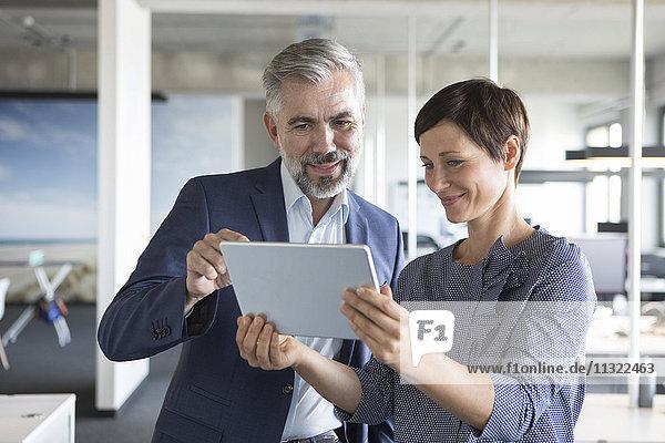 Geschäftsmann und Geschäftsfrau mit Tablette im Büro