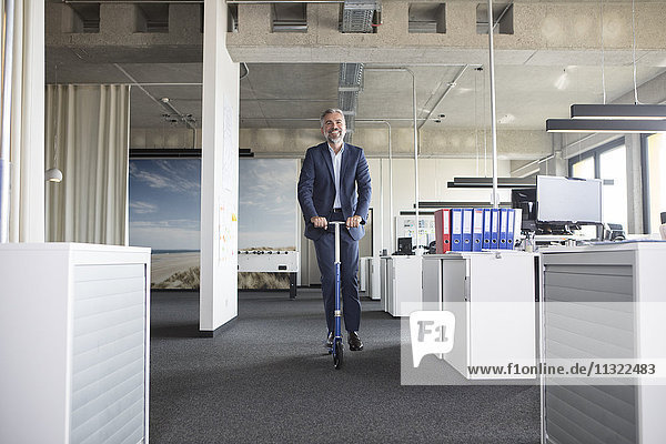 Geschäftsmann auf Roller im Büro