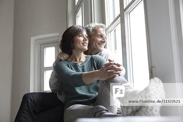 Lächelndes reifes Paar schaut aus dem Fenster