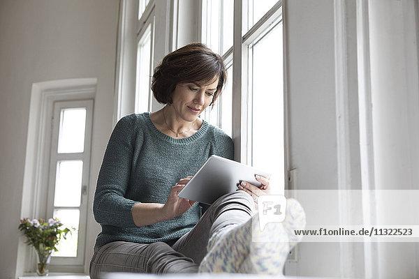 Frau mit Tablette am Fenster