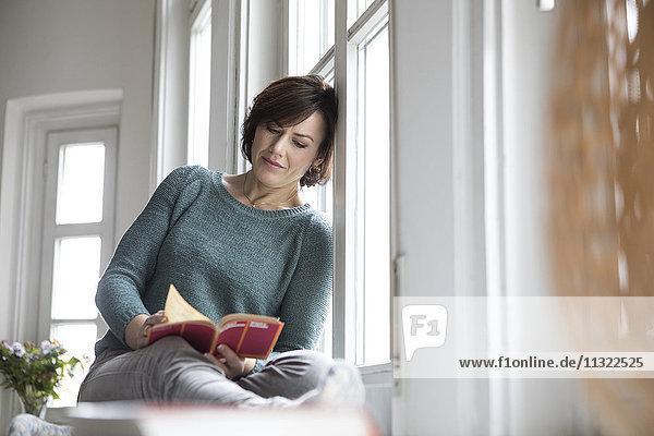 Frau liest Buch am Fenster