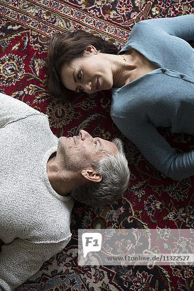 Auf Teppich liegendes reifes Paar