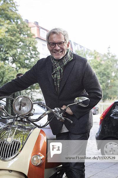 Lächelnder reifer Mann mit Motorroller