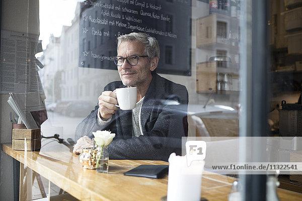 Erwachsener Mann trinkt Kaffee in einem Cafe