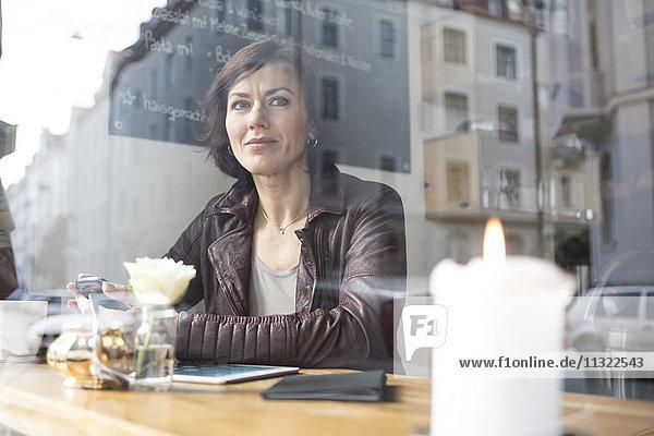 Frau in einem Café mit Blick aus dem Fenster