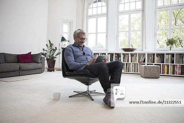 Der reife Mann zu Hause sitzt auf dem Stuhl mit Tablette
