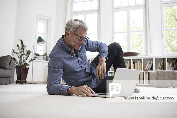 Erwachsener Mann zu Hause auf dem Boden liegend mit Laptop