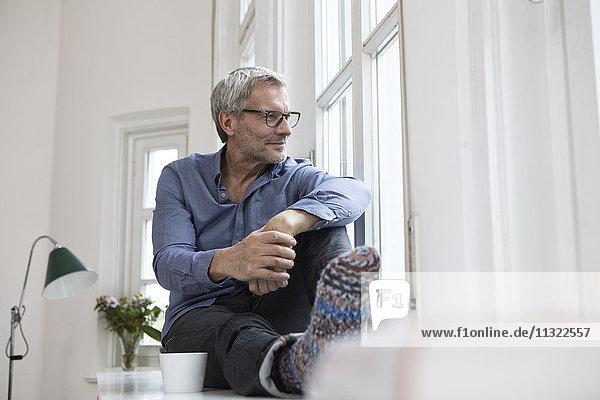 Entspannter reifer Mann zu Hause  der aus dem Fenster schaut.