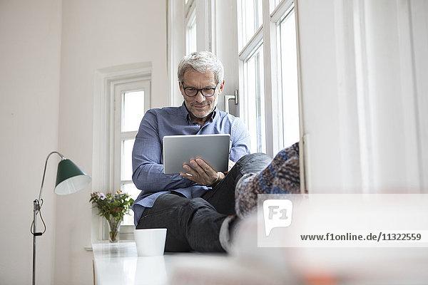 Erwachsener Mann zu Hause am Fenster sitzend mit Tablette