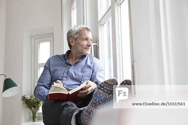 Entspannter reifer Mann zu Hause mit Blick aus dem Fenster