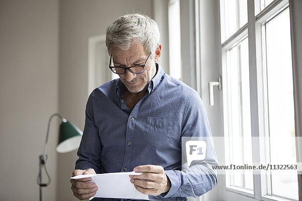 Reifer Mann am Fenster beim Lesen von Dokumenten