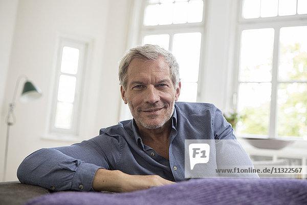 Porträt eines reifen Mannes zu Hause auf dem Sofa