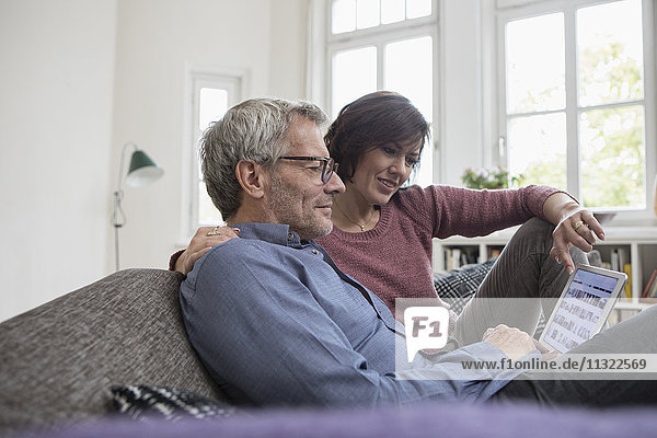 Mature couple at home on the sofa sharing tablet