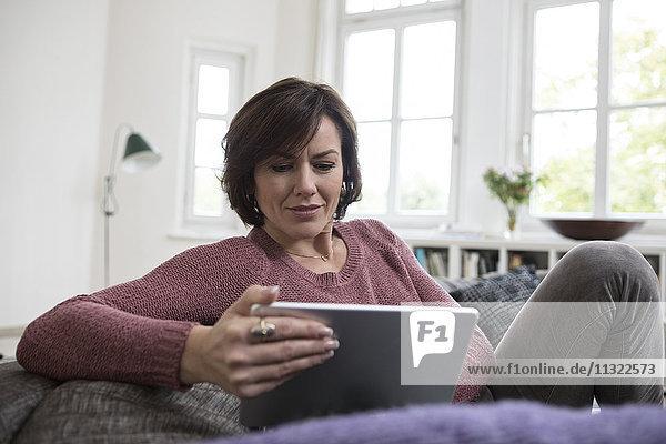 Frau zu Hause auf dem Sofa sitzend mit Tablette
