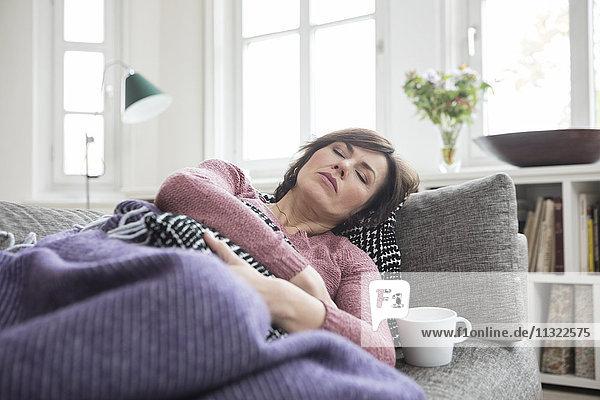 Frau mit Bauchschmerzen auf dem Sofa liegend