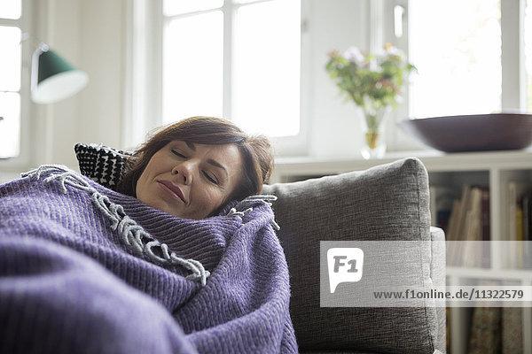 Frau mit Decke auf dem Sofa liegend