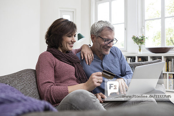 Smiling mature couple at home on the sofa shopping online