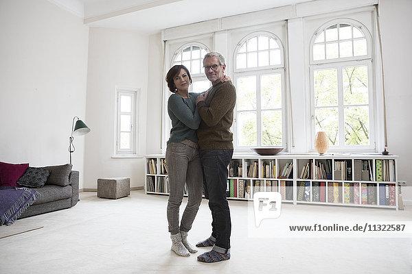 Erwachsenes Paar im Wohnzimmer stehend