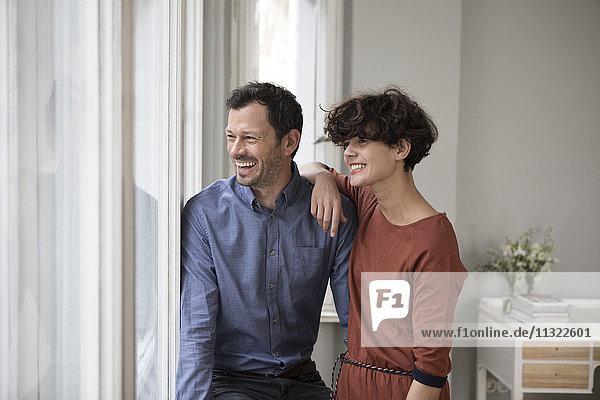 Lachendes Paar schaut zu Hause durchs Fenster