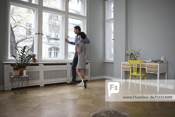 Paar schaut gemeinsam durchs Fenster nach Hause
