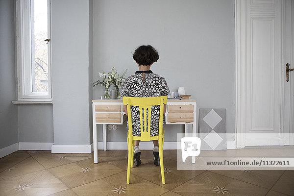 Rückansicht einer jungen Frau  die auf einem gelben Stuhl zu Hause sitzt.