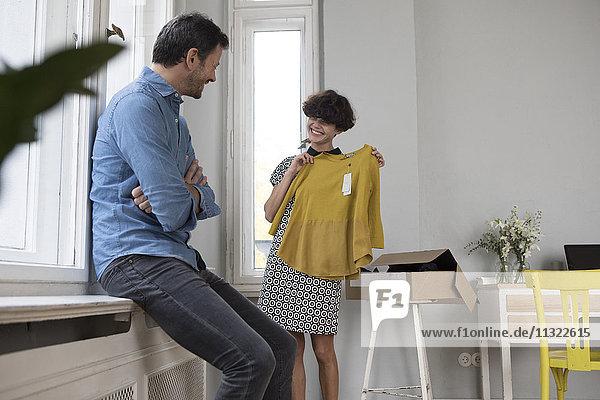 Glückliche Frau präsentiert ihren neuen Pullover zu Hause