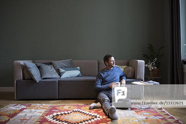 Mann sitzt auf dem Boden in seinem Wohnzimmer und schaut durchs Fenster.
