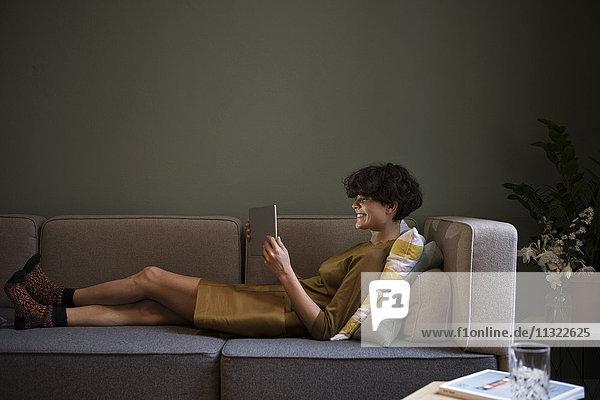 Lächelnde junge Frau mit Tablette auf der Couch zu Hause