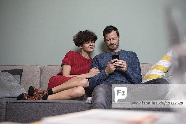 Paar sitzt zusammen auf der Couch und schaut auf das Handy