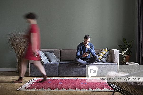 Mann sitzt auf der Couch im Wohnzimmer  während seine Freundin im Vordergrund vorbeigeht.