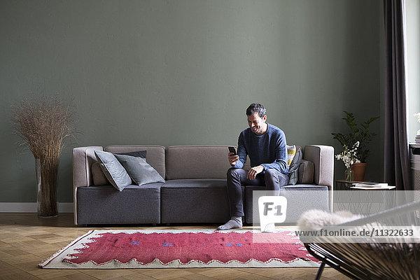 Mann auf der Couch im Wohnzimmer mit Blick auf das Smartphone