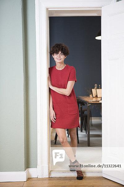 Porträt einer lächelnden jungen Frau  die sich zu Hause an den Türrahmen lehnt.