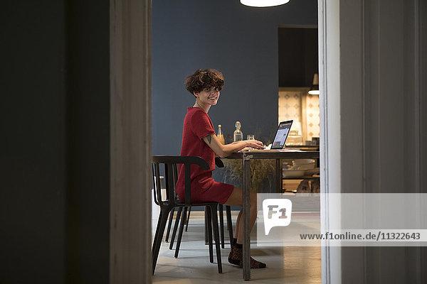 Lächelnde junge Frau sitzend in der Küche mit Laptop