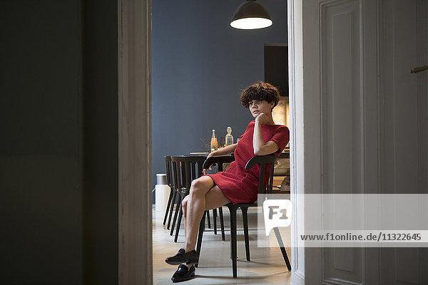 Nachdenkliche junge Frau sitzt in der Küche.