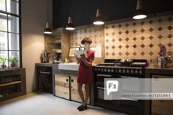 Junge Frau stehend in der Küche mit Tablette