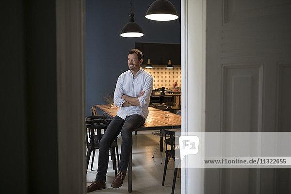 Lächelnder Mann sitzt auf dem Tisch in seiner Küche.