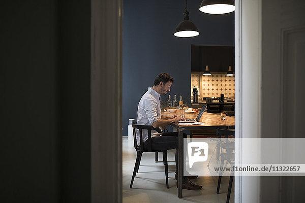 Mann sitzt in seiner Wohnküche mit Laptop