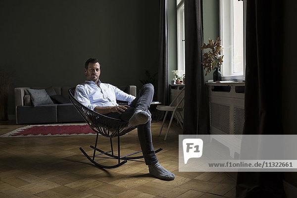 Porträt eines Mannes auf Schaukelstuhl im Wohnzimmer
