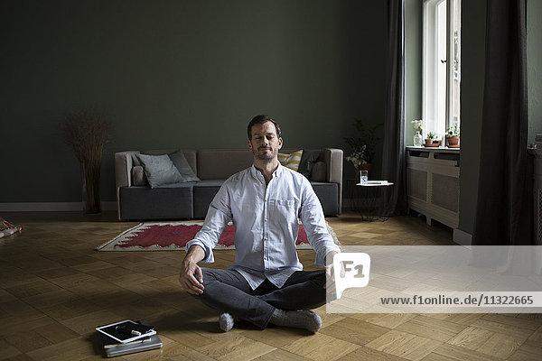 Meditierender Mann auf dem Boden zu Hause