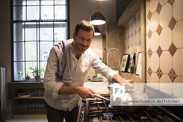 Porträt des lächelnden Mannes beim Kochen zu Hause