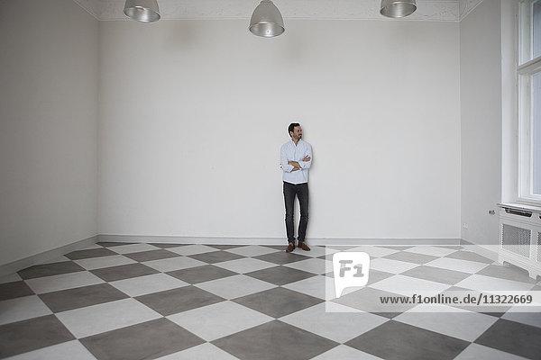 Mann steht im leeren Raum und schaut durchs Fenster.
