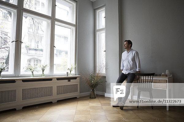Mann schaut durchs Fenster nach Hause