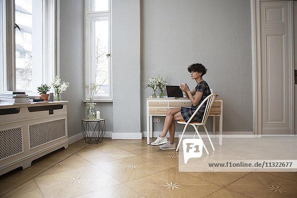 Junge Frau sitzt zu Hause am Schreibtisch und schaut durchs Fenster.