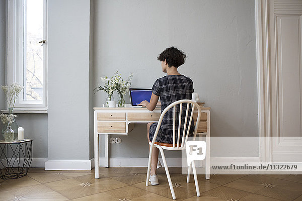 Rückansicht der jungen Frau am Schreibtisch zu Hause mit Laptop
