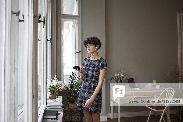 Porträt einer jungen Frau mit Smartphone und Kopfhörer zu Hause