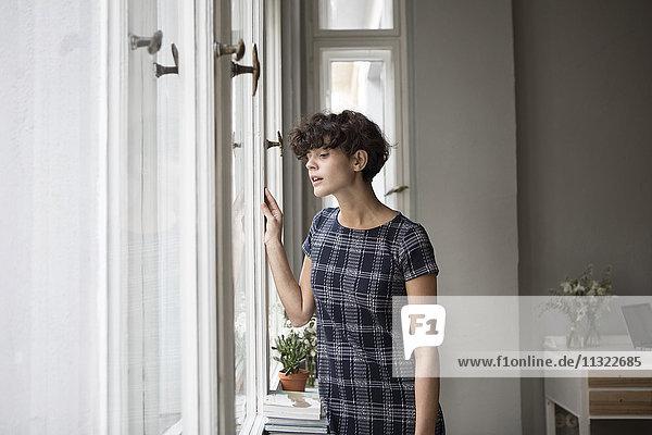 Porträt einer jungen Frau  die zu Hause durchs Fenster schaut.