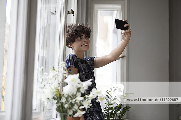 Lächelnde junge Frau steht vor dem Fenster und nimmt Selfie mit dem Smartphone.